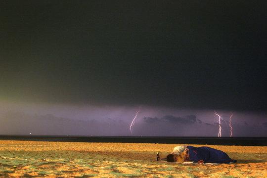 Lightning in the distance as couple sleeps on beach on the Black Sea shore of Vama Veche, Romania