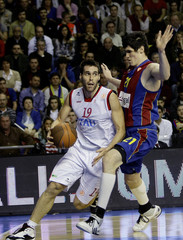 Tau Ceramica's Fernando San Emeterio goes to the basket as Barcelona's Ersan Ilyasova tries to block him in Barcelona