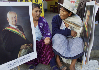 BOLIVIAN INDIAN WOMEN CHATS HOLDING POSTERS OF PRSIDENT BANZER.