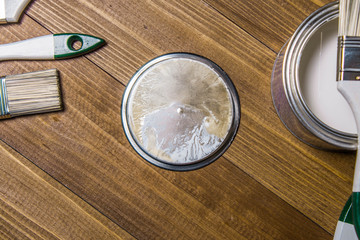A set of white paint brushes, a metal can with white paint on a wooden texture table