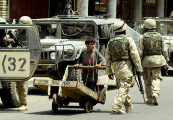 AN IRAQI BOY PUSHES A CART PAST U.S. ARMY SOLDIERS ON PATROL INBAGHDAD.