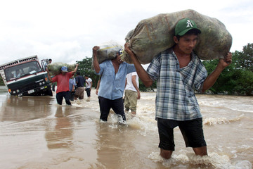 Residents carry food down the flooded Pan-American highway, caused by Hurricane Keith, north-west of..