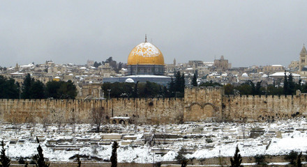 Snow covers Jerusalem's old city with the Dome of the Rock in the background February 25, 2003. Heav..
