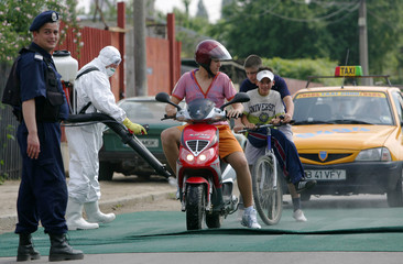 A sanitary worker sprays a disinfectant solution on a motorcycle on the outskirts of Bucharest