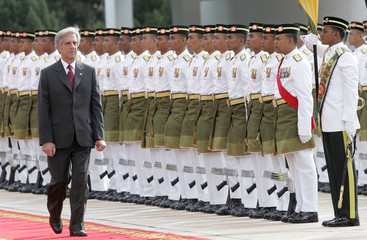 Uruguay's President Vazquez inspects the guard of honour at Malaysia's Parliament Square in Kuala Lumpur