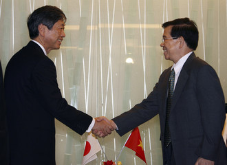 Vietnam's President Nguyen Minh Triet greets Japanese Foreign Minister Masahiko Komura prior to their meeting at a Tokyo hotel