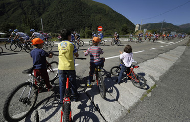 "Children on bicycles look at a pack of riders during stage 15 of the Tour of Spain ""La Vuelta"" cycling race between Cudillero and Ponferrada"