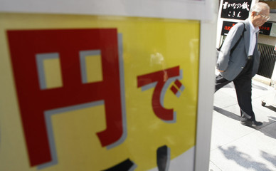 A symbol of Japanese Yen is seen at a promotional poster of a shop in Tokyo