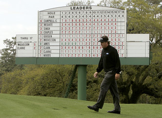 Phil Mickelson of US walks to 18th green with scoreboard in background during rain-delayed third round of Masters golf tournament in Augusta