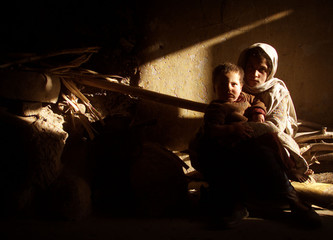 An Afghan girl Sarina holds her brother in their humble refugee home in a suburb of Kabul December 8..