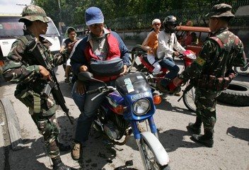 Filipino soldiers inspect people and vehicles at a checkpoint in Cotabato city, southern Philippines