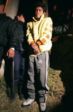 Mexican police stand next to a suspected burglar whom villagers tied to a post in a village in the Naucalpan district