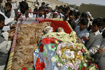 Afghans carry the bodies of two children who they say were killed by U.S-led troops in Kabul