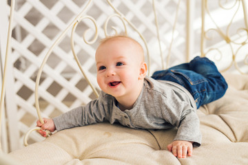 Adorable laughing baby boy in sunny bedroom. Newborn child relaxing. Nursery for young children.Family morning at home. Little kid lying on tummy