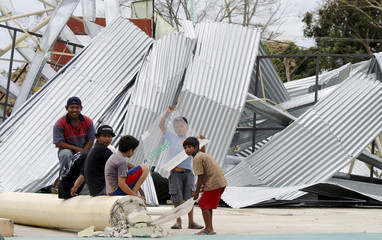 Boys sit next to a structure destroyed by hurricane Dean in the community of Limones