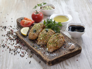 Chicken fillet in marinade on a wooden board.