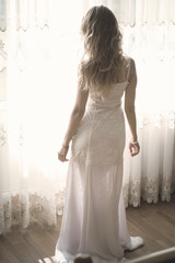 A lonely bride in a white tight-fitting dress and blond hair at home, misses her ladder in the room, waits for her fiance