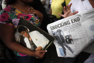 A woman holds a copy of the album 'Thriller' and another carries a local newspaper as fans commemorate pop icon Michael Jackson at the Apollo Theater in New York