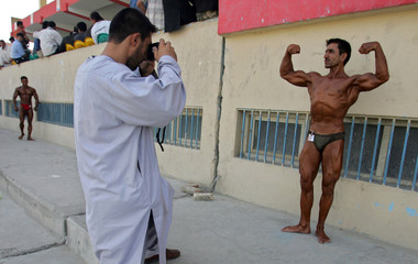 A man photographs a body builder as he poses before a competition for the title of Mr Afghanistan in Kabul