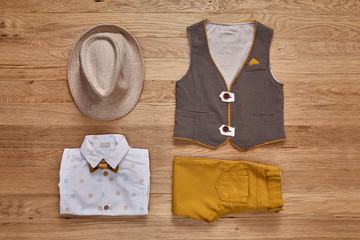 Top view of the kids fashion clothes with accessories on the wooden background.