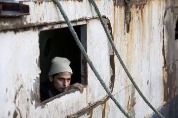 Migrant looks out of window of Marine 1 vessel at the port of Nouadhibou