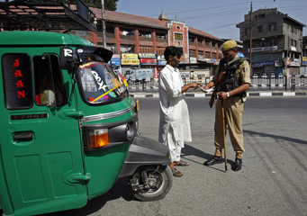 An Indian police officer checks the curfew pass of a Kashmiri rickshaw driver on the fourth consecutive day of a curfew in Srinagar