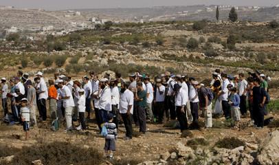 Right-wing Israeli activists pray on a hilltop near near Hebron