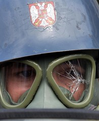 A policeman looks through broken glass on a tear gas mask while standing in a cordon after a small c..