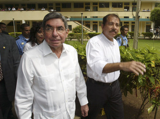 Costa Rica's President Arias and Nicaragua's President Ortega walk at Catholic University in Managua