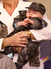 BABY DRESSED IN CAMOFLAUGE FATIGUES DURING MILITARY PARADE IN BRASILIA.