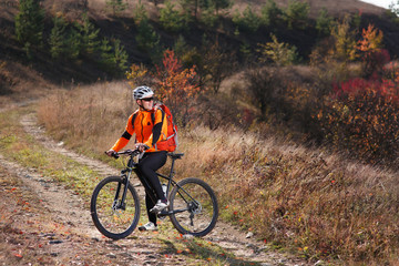 Portrait of young cyclist riding bicycle along trail in the countryside.