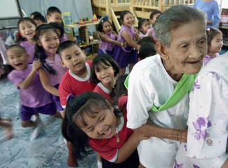 AN ELDERLY THAI WOMAN JOINS IN A TRADITIONAL CHILDRENS GAME AT ABANGKOK SCHOOL.