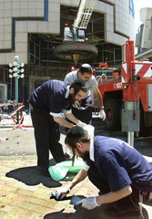 MEMBERS OF A JEWISH FUNERAL SERVICE SEARCH THE SCENE OF A BOMB BLAST IN NETANYA.