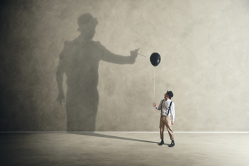 man and shadow with black balloon