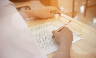 students writing test exam on paper for Admissions in high school with uniform student in School classroom of Thailand, exam student background and education concept