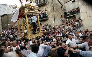 About a hundred men run through the southern Sicilian town of Capizzi carrying a heavy platform ...