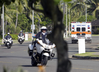 An ambulance and police drive on street where U.S. President Obama is staying in Kailua, Hawaii