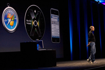 Apple's Chief Executive Steve Jobs stands in front of a screen with pictures of Safari, Leopard, and iPhone at the company's World Wide Developers Conference in San Francisco