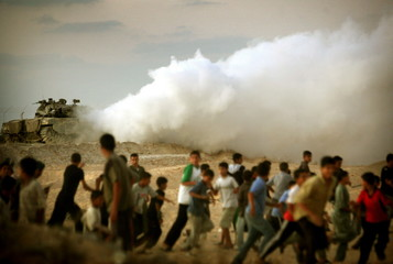 Palestinians run from an Israeli army tank guarding the Jewish settlement of Neve Dekalim, southern ..