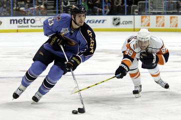 Atlanta Thrashers Slater skates past New York Islanders Comrie during the third period of play of their NHL hockey game in Atlanta