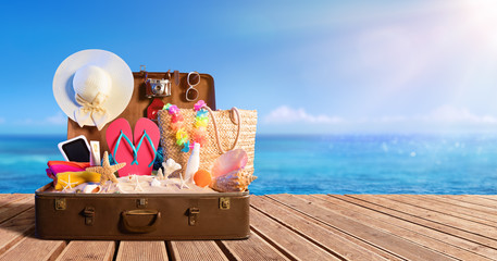 Fototapete - Beach Accessories In Suitcase On Beach - Travel Concept