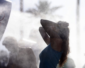 A concert-goer stands in a water mist during the Coachella Music Festival in Indio