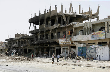 Residents walk past buildings destroyed during fighting  in Baghdad's Sadr City