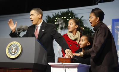 U.S. President Barack Obama reacts beside family as they light the National Christmas Tree on the Ellipse in Washington
