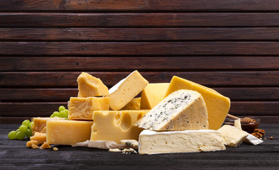 Various types of cheese on black wooden table.