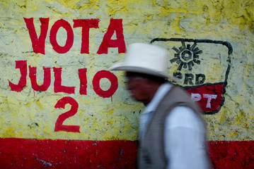 Elderly man walks past wall painted with symbol of Party of the Democratic Revolution in Mexico City