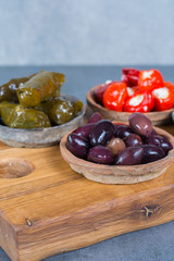 Mediterranean appetizer antipasti tapas bowls with green and calamata olives, feta cheese, stuffed pepper, herbs on wooden plank