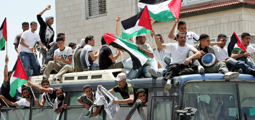Freed Palestinian prisoners celebrate and wave Palestinian flags as they arrive at Ramallah.