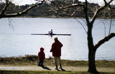 A woman and boy watch a rower on the Charles River in Cambridge