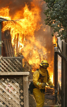 A California Department of Forestry firefighter works with axe on fire n Rancho Santa Fe near San Diego